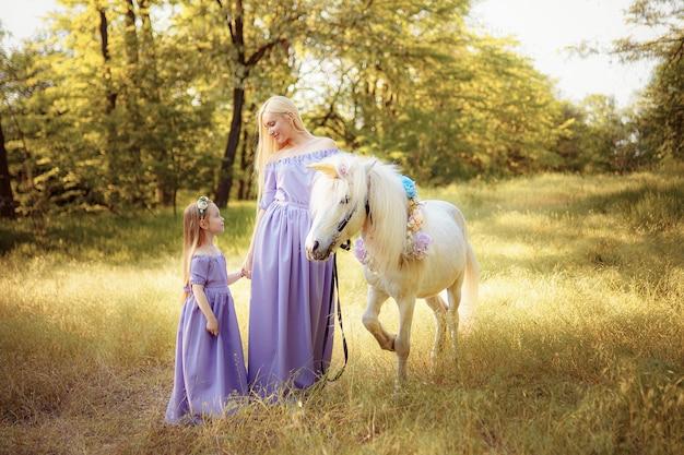 Mère et fille dans des robes lavande similaires caressent un cheval licorne. prairie d'été