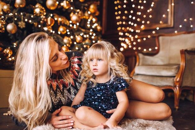 Mère et fille dans des vêtements brillants étreignant et souriant, soirée d'hiver ensemble à la maison dans un salon décoré à la veille de noël.