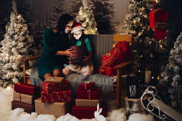 Mère avec fille déballer le cadeau de noël.