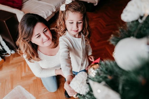 Mère et fille décorant l'arbre de noël à la maison