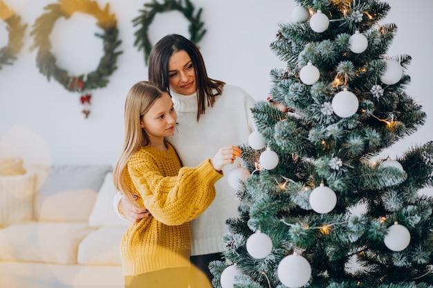 Mère avec fille décoration arbre de noël