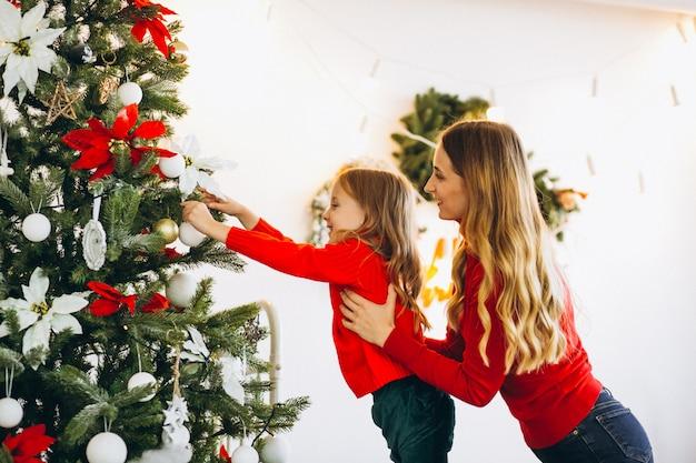 Mère avec fille décorer un arbre de noël