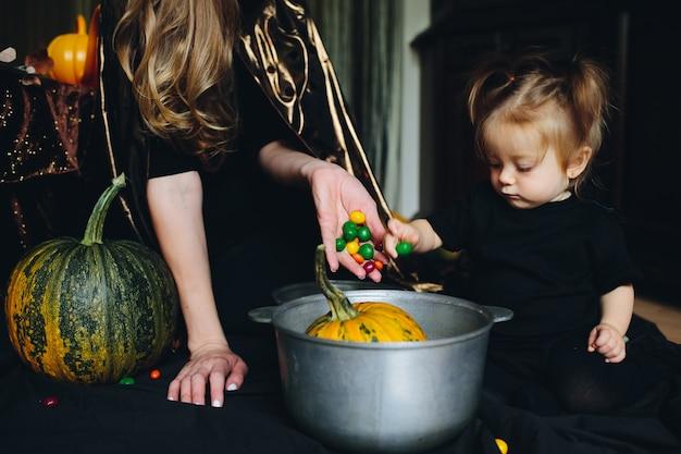 Mère et fille décorer une citrouille dans un bol