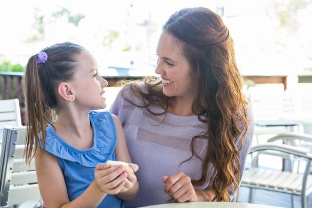 Mère et fille dégustant des gâteaux à la terrasse du café