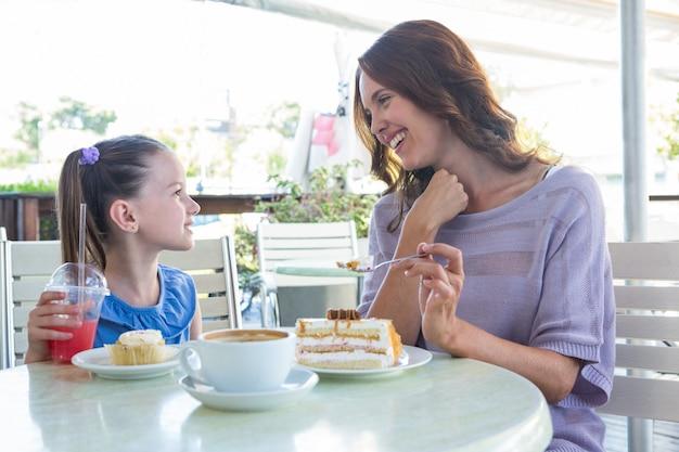 Mère et fille en dégustant des gâteaux à la terrasse du café