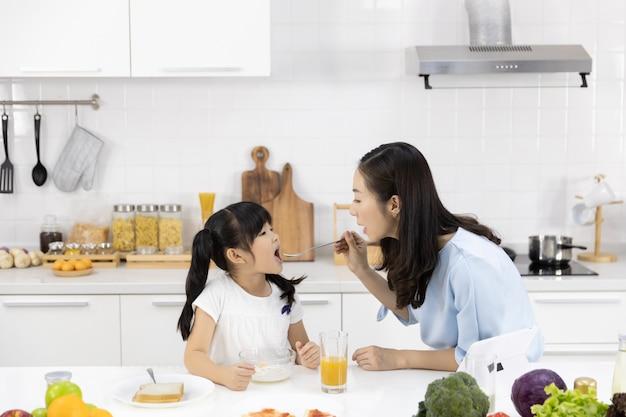 Mère et fille déjeunent et regardent les médias dans une tablette