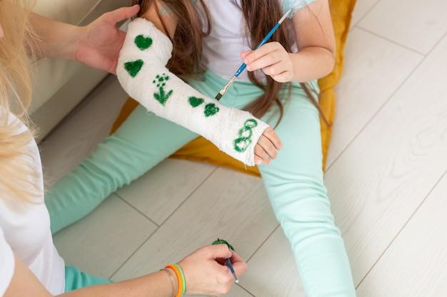 Mère et fille dessin photo sur un bandage à l'aide de peintures concept de thérapie par le jeu en gros plan
