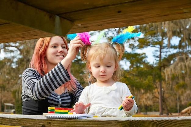 Mère et fille dessinant des couleurs dans un parc