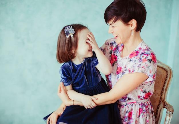 La mère avec la fille embrassant et assis sur la chaise