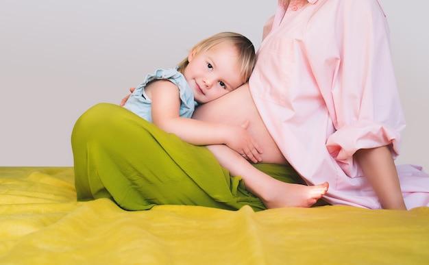 Mère et fille enceintes ensemble à la maison femme avec son premier enfant pendant la deuxième grossesse