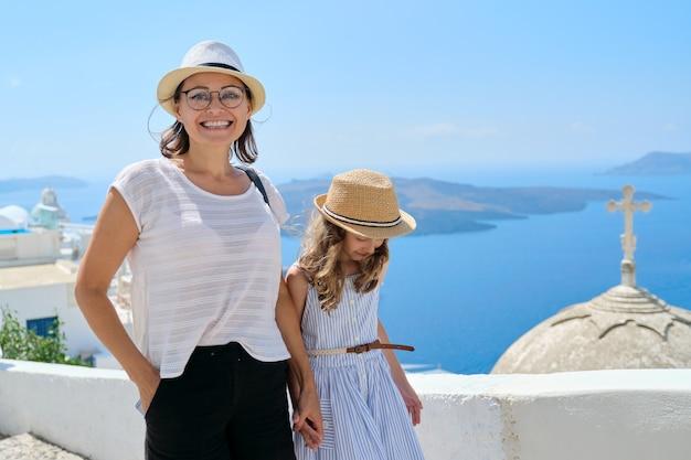 Mère et fille enfant, famille de voyage heureuse marchant ensemble, tenant la main sur la célèbre île grecque touristique de santorin. ciel, mer, fond de dôme d'église