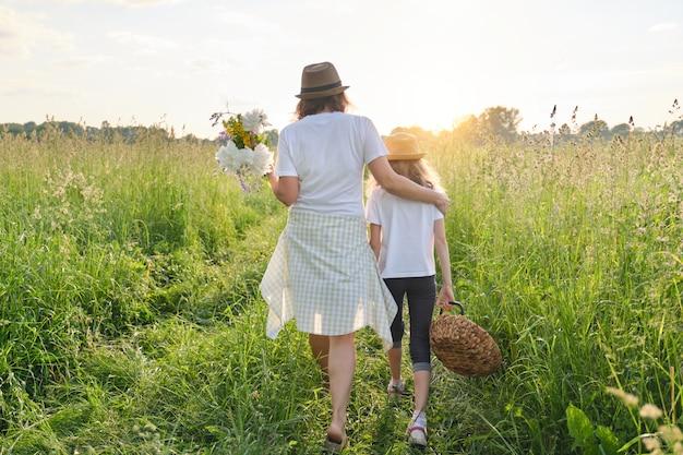 Mère et fille enfant marchant le long du pré, vue de l'arrière