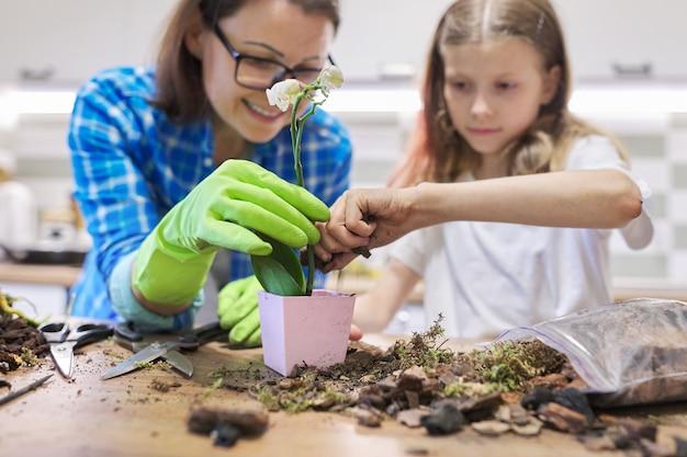 Mère et fille enfant plantant des plantes d'orchidées phalaenopsis dans des pots ensemble