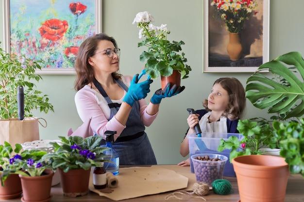 Mère et fille enfant plante des plantes en pot, des fleurs. loisirs et loisirs, soins, famille, plante d'intérieur, concept d'amis en pot à la maison