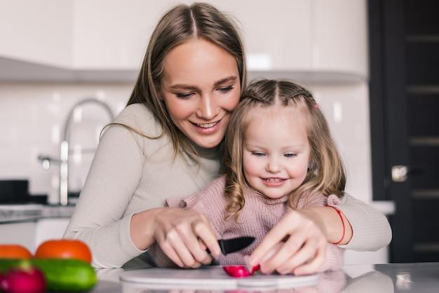 Mère et fille enfant préparent la salade de légumes