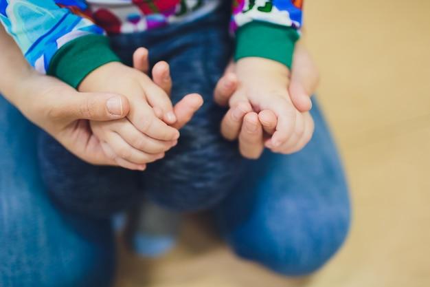Mère et fille enfant tenant la main avec amour dans le ton de couleur vintage.
