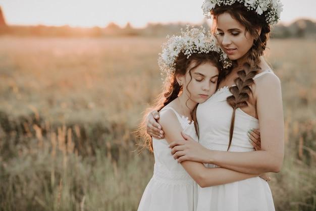 Mère et fille ensemble dans des robes blanches avec des tresses et des couronnes florales dans le style boho dans le champ de l'été au coucher du soleil