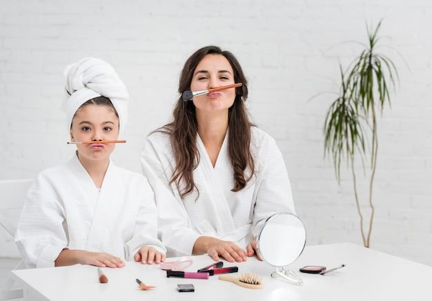 Mère et fille étant idiote avec des pinceaux à maquillage