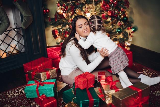 Mère et fille étreignant en tas de cadeaux.