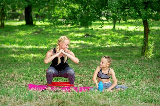Mère et fille faisant des exercices sportifs sur le tapis dans le parc en plein air