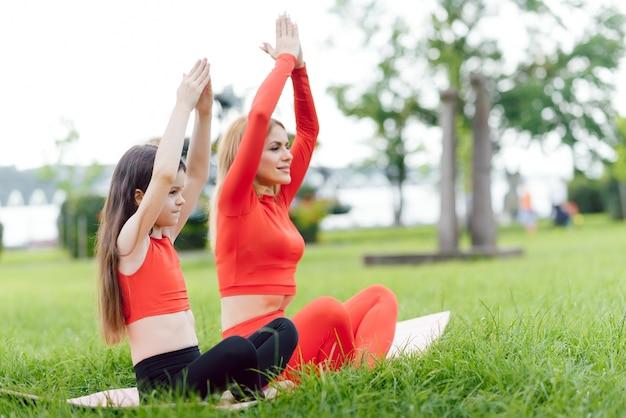 Mère et fille faisant des exercices de yoga sur l'herbe dans le parc à la journée