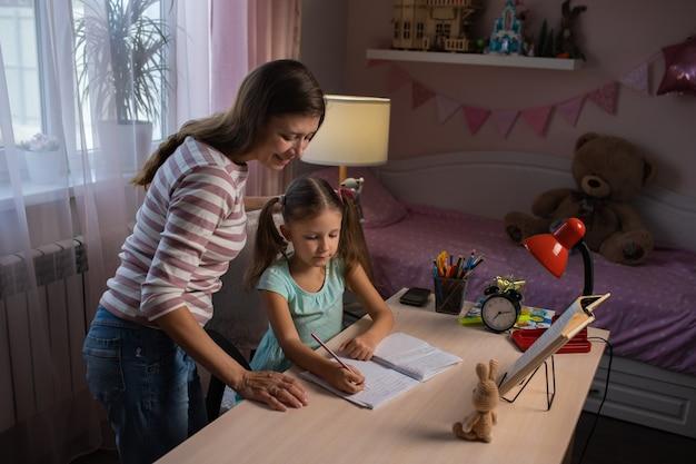Mère et fille faisant leurs devoirs ensemble à la maison. maman aide sa fille à faire ses devoirs