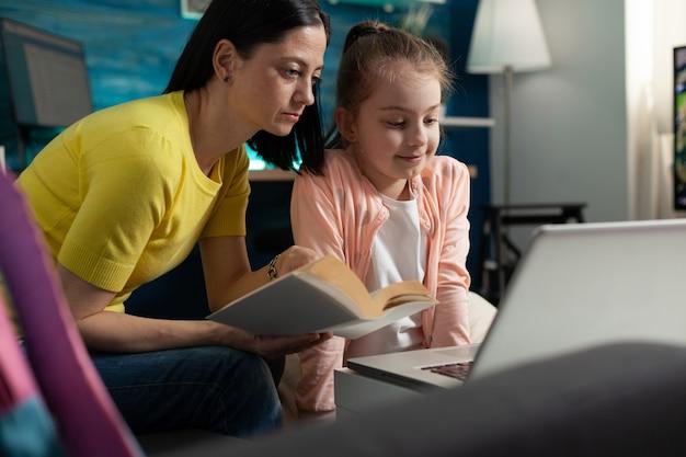 Mère et fille faisant leurs devoirs pour l'école en ligne