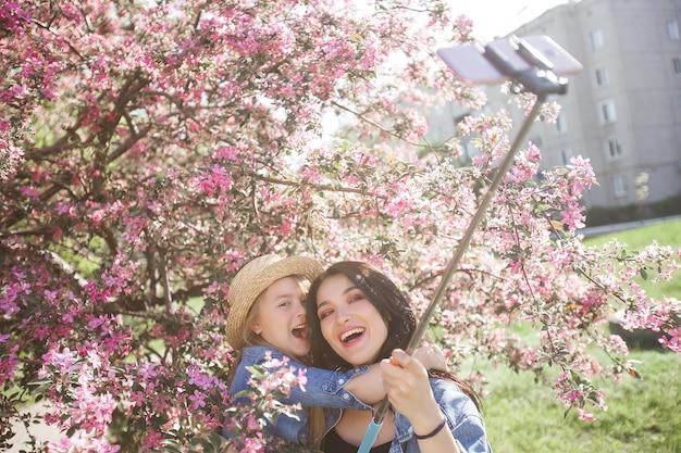 Mère et fille faisant selfie au parc. filles tirant sur téléphone portable