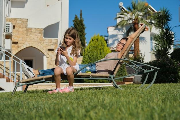 Mère et fille de famille heureuse au repos assis sur une chaise extérieure