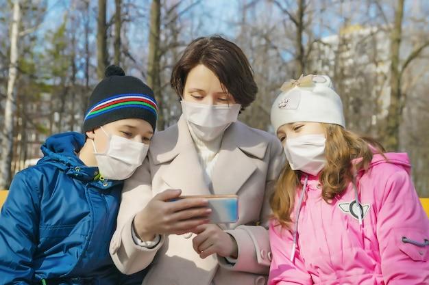 Mère avec fille et fils dans des masques médicaux de protection contre les virus dans la rue avec téléphone mobile
