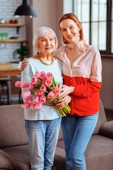 Mère et fille avec des fleurs. plan complet d'une dame vieillissante aux cheveux gris à la retraite en sweetshirt bleu et jeans tenant des tulipes et posant avec une belle dame mature en chemisier rose