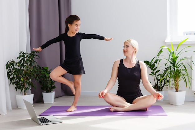 Mère et fille font des exercices de yoga en ligne avec un ordinateur portable à la maison