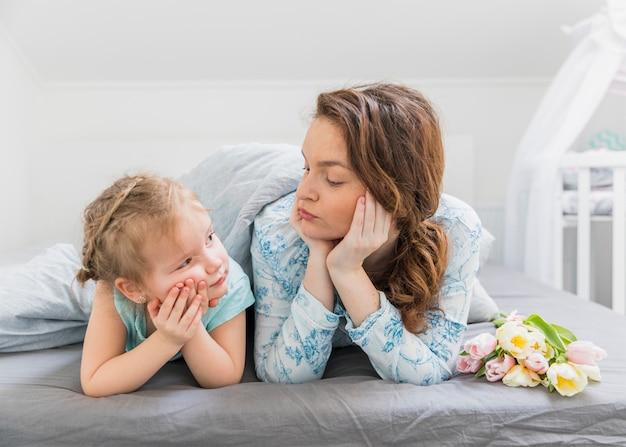 Mère et fille froncées en se regardant au lit à la maison