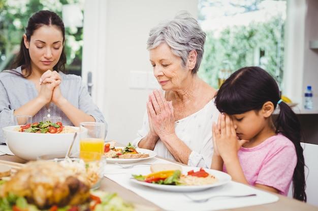 Mère et fille avec grand-mère priant à la table à manger