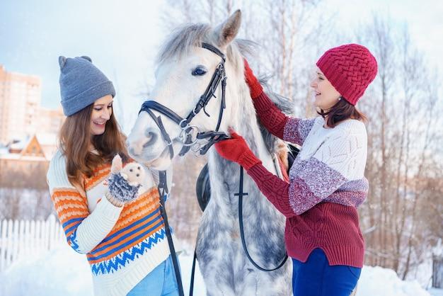Mère et fille en hiver avec un beau cheval blanc