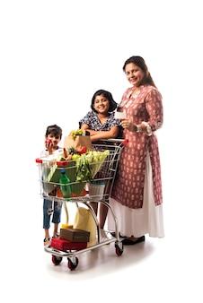 Mère et fille indiennes avec panier ou chariot isolés sur mur blanc