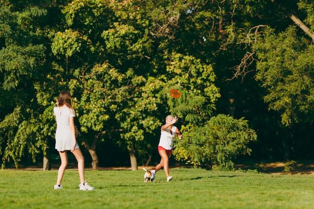 Mère et fille jetant un disque volant orange à un petit chien drôle, qui l'attrape sur l'herbe verte. little jack russel terrier animal jouant à l'extérieur dans le parc. chien et femmes. famille reposant en plein air