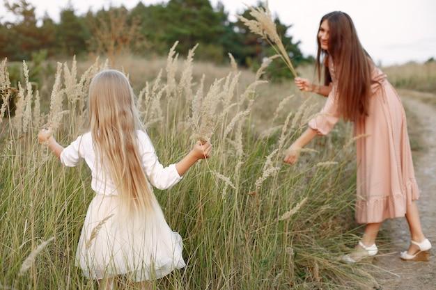 Mère avec fille jouant dans un champ d'automne
