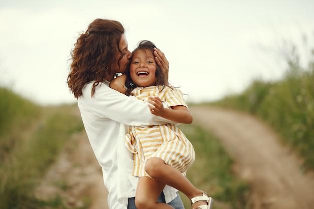 Mère avec fille jouant dans un champ d'été