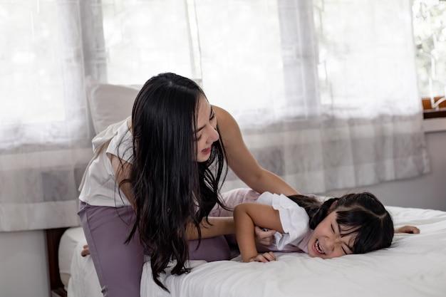 Mère et fille jouant dans le lit de la chambre.