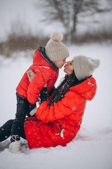 Mère et fille jouant dans le parc d'hiver