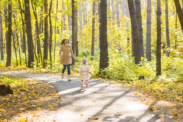 Mère et fille jouant ensemble dans le parc en automne.