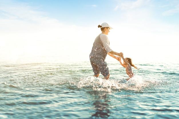 Mère et fille jouant à la mer. loisirs d'été actifs pendant les vacances. maman et enfant s'amusant sur l'eau. tenant ses enfants sur les mains et la tordant.