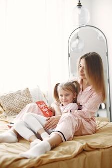 Mère et fille jouissant sur le lit. tenant une boîte cadeau rouge. fête des mères.