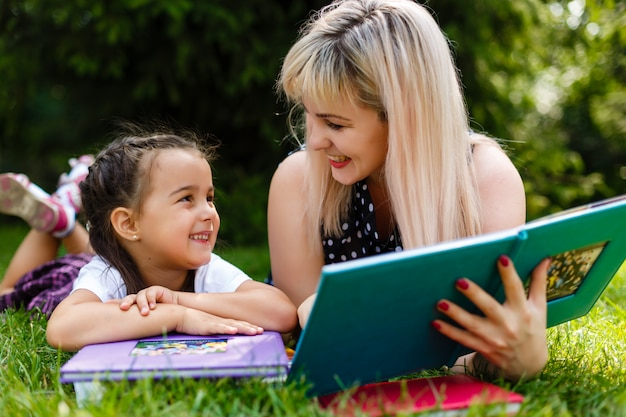 Mère et fille lisant un livre au parc.