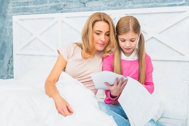 Mère, fille, lit, regarder, papiers