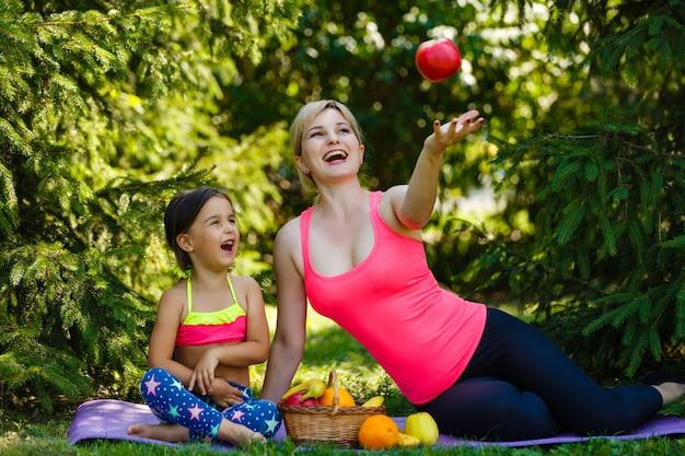 Mère et fille mangeant des fruits dans le parc après une séance d'entraînement