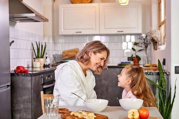 Mère et fille mangeant des fruits et du porridge. alimentation saine pour les enfants, repas du matin famille caucasienne prenant son petit déjeuner dans une cuisine moderne et légère