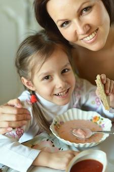 Mère et fille mangeant de la soupe à table à la maison