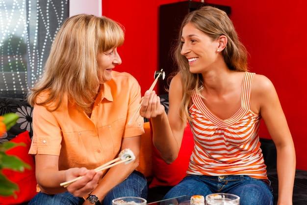 Mère et fille mangeant des sushis